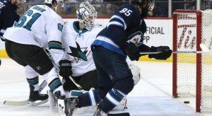Jets forward Mathieu Perrault slips a puck past Sharks goaltender Martin Jones