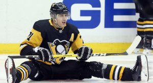 Evgeni Malkin attempts to pick himself up off the ice after falling to the ground.