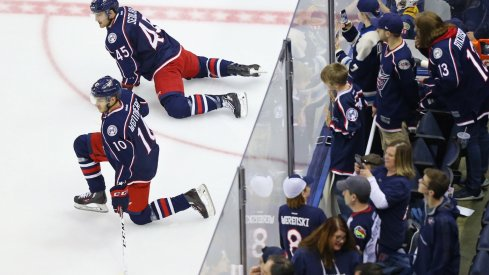 Alexander Wennberg and Lukas Sedlak stretch as fans look on