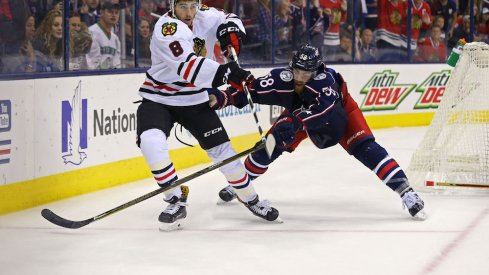 David Savard of the Blue Jackets defends against Nick Schmaltz of the Blackhawks