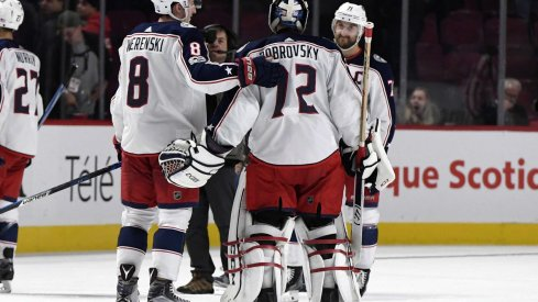 Sergei Bobrovsky meets with Zach Werenski and Nick Foligno at center ice after a victory
