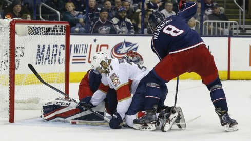 Zach Werenski tries to clear the puck against the Florida Panthers