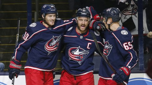 Alexander Wennberg and Nick Foligno celebrate with Markus Nutivaara after scoring a goal