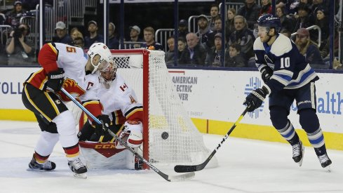 Alexander Wennberg tries to put the puck on net with Mark Giordano trying to track him down