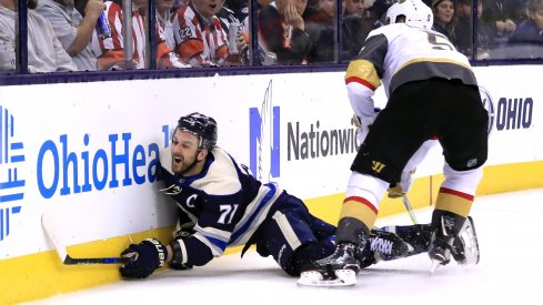Nick Foligno goes head first into the boards after being checked by the Vegas Golden Knights' Derek Engelland.
