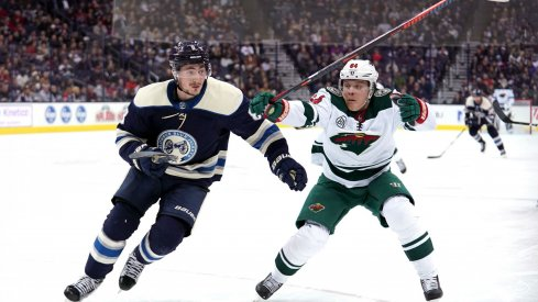 Zach Werenski and Markus Granlund chase after a puck as the Columbus Blue Jackets play the Minnesota Wild
