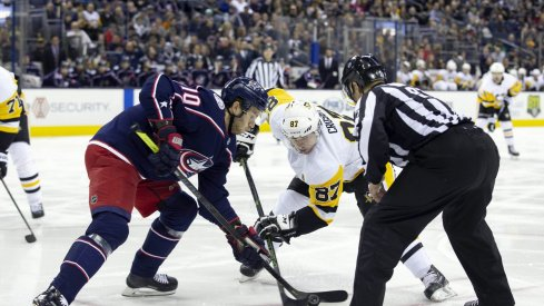 Pittsburgh Penguins center Sidney Crosby (87) and Columbus Blue Jackets center Alexander Wennberg (10) face-off during the first period at Nationwide Arena.