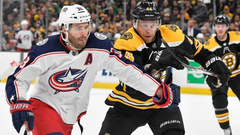 Columbus Blue Jackets center Boone Jenner fights for the puck against the Boston Bruins during a game at TD Garden.