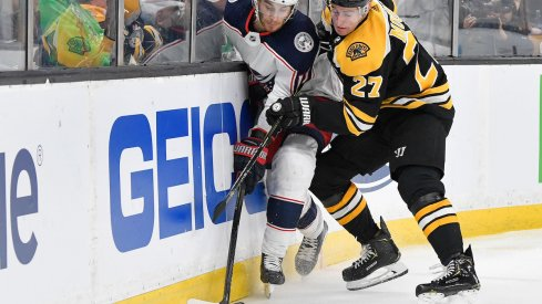Columbus Blue Jackets center Alexander Wennberg fights for the puck against Boston Bruins defenseman John Moore.