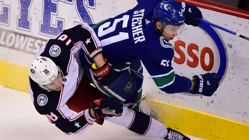 Blue Jackets' Pierre-Luc Dubois fights for the puck against Canucks defenseman Troy Stecher