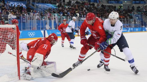 Feb 16, 2018; Gangneung, South Korea; Olympic Athlete of Russia defenseman Vladislav Gavrikov (4) and Slovenia forward Miha Verlic (91) battle for the puck in front of Olympic Athlete of Russia goalkeeper Ilya Sorokin (31) during the third period at the Pyeongchang 2018 Olympic Winter Games at Gangneung Hockey Centre.