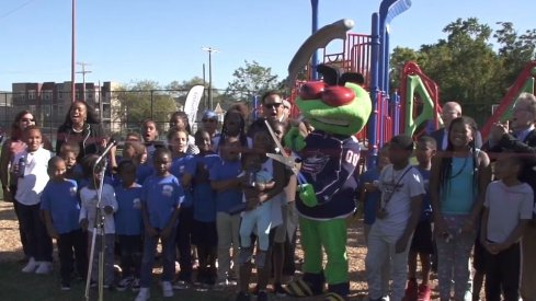 Stinger cuts the ribbon for a new playground that was built.