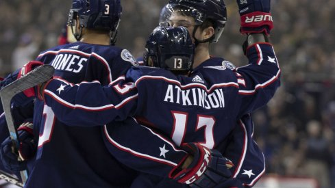 Columbus Blue Jackets forward Cam Atkinson celebrates an empty net goal with Seth Jones in a regular season contest against the Pittsburgh Penguins at Nationwide Arena during March of 2019.