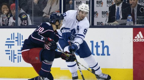 Columbus Blue Jackets center Alexander Wennberg defends against Toronto Maple Leafs center John Tavares during a game at Nationwide Arena.