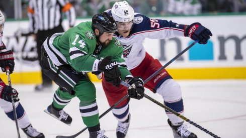 Dallas Stars left wing Jamie Benn (14) and Columbus Blue Jackets defenseman David Savard (58) chase the puck during the third period at the American Airlines Center.