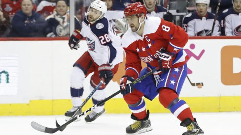 Columbus Blue Jackets forward Oliver Bjorkstrand fights for the puck against Alexander Ovechkin of the Washington Capitals.