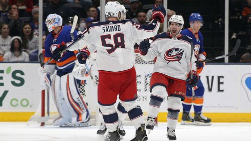 Dec 23, 2019; Uniondale, New York, USA; Columbus Blue Jackets left wing Nathan Gerbe (24) celebrates his goal against New York Islanders goalie Thomas Greiss (1) with Blue Jackets defenseman David Savard (58) during the second period at Nassau Veterans Memorial Coliseum.