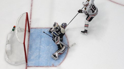 Dec 29, 2019; Columbus, Ohio, USA; Chicago Blackhawks center Jonathan Toews (19) slides the puck under Columbus Blue Jackets goalie Joonas Korpisalo (70) for goal during the shootout at Nationwide Arena. Mandatory Credit: Russell LaBounty-USA TODAY Sports