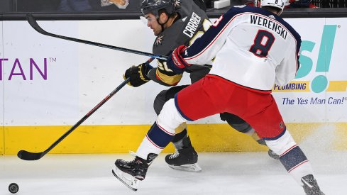 Columbus Blue Jackets defenseman Zach Werenski (8) checks Vegas Golden Knights left wing William Carrier (28) during the first period at T-Mobile Arena