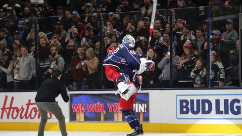 Columbus Blue Jackets goalie Elvis Merzlikins (90) and Columbus Blue Jackets left wing Nick Foligno (71) celebrate the win over the Carolina Hurricanes after the game at Nationwide Arena.