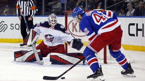Jan 19, 2020; New York, New York, USA; Columbus Blue Jackets goaltender Matiss Kivlenieks (80) defends against New York Rangers defenseman Brendan Smith (42) during the second period at Madison Square Garden.