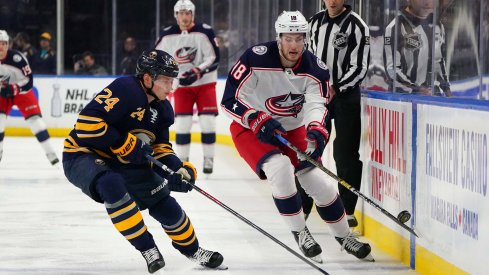 Mar 31, 2019; Buffalo, NY, USA; Buffalo Sabres defenseman Lawrence Pilut (24) and Columbus Blue Jackets center Pierre-Luc Dubois (18) go after a loose puck during the first period at KeyBank Center.