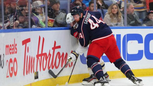 Feb 13, 2020; Buffalo, New York, USA; Columbus Blue Jackets defenseman Vladislav Gavrikov (44) pins Buffalo Sabres left wing Victor Olofsson (68) on the boards as he goes for the puck during the second period at KeyBank Center.