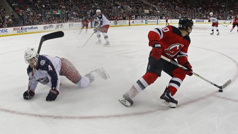 New Jersey Devils center Blake Coleman (20) plays the puck against Columbus Blue Jackets defenseman Scott Harrington (4) during the second period at Prudential Center.