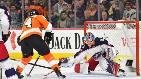 Feb 18, 2020; Philadelphia, Pennsylvania, USA; Columbus Blue Jackets goaltender Elvis Merzlikins (90) makes a save against Philadelphia Flyers center Sean Couturier (14) during the second period during the first period at Wells Fargo Center. Mandatory Credit: Eric Hartline-USA TODAY Sports