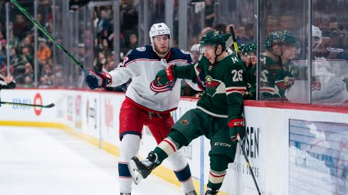 Feb 25, 2020; Saint Paul, Minnesota, USA; Columbus Blue Jackets forward Pierre-Luc Dubois (18) checks Minnesota Wild forward Gerald Mayhew (26) in the second period at Xcel Energy Center.