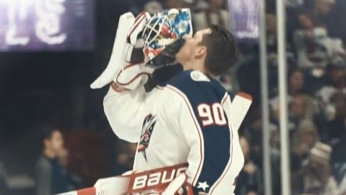 Elvis Merzlikins kisses his helmet before he goes back into the net for the Columbus Blue Jackets.