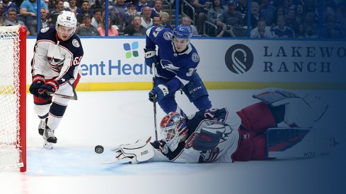 Columbus Blue Jackets goaltender Sergei Bobrovsky reaches for a puck as Yanni Gourde of the Tampa Bay Lightning approaches during Game 1 at Amalie Arena.