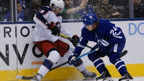 Zach Werenski and Kasperi Kapanen battle for the puck