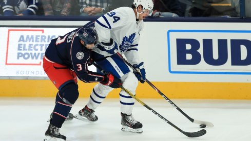 Seth Jones battles for the puck against Auston Matthews
