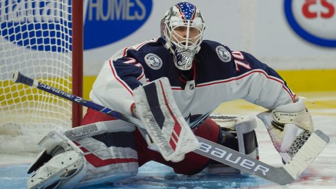 Columbus Blue Jackets goaltender Joonas Korpisalo stretches between stoppages in play.