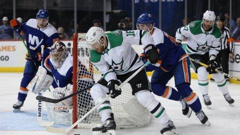 Joe Pavelski plays the puck against New York Islanders goalie Semyon Varlamov