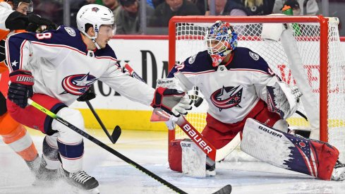 Feb 18, 2020; Philadelphia, Pennsylvania, USA; Columbus Blue Jackets defenseman Zach Werenski (8) reaches for the puck in front of goaltender Elvis Merzlikins (90) against the Philadelphia Flyers during the second period during the first period at Wells Fargo Center.