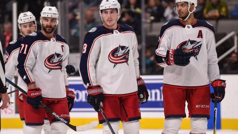 Nick Foligno, Zach Werenski, Seth Jones, and Emil Bemstrom before a faceoff