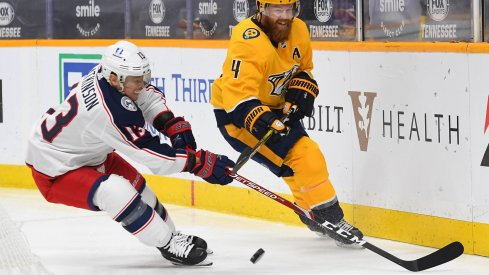 Jan 16, 2021; Nashville, Tennessee, USA; Nashville Predators defenseman Ryan Ellis (4) hits the puck past Columbus Blue Jackets right wing Cam Atkinson (13) during the second period at Bridgestone Arena.