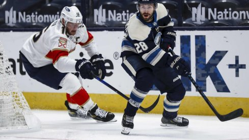 Jan 26, 2021; Columbus, Ohio, USA; Florida Panthers center Aleksander Barkov (16) skates as Columbus Blue Jackets right wing Oliver Bjorkstrand (28) passes the puck in the first period at Nationwide Arena.