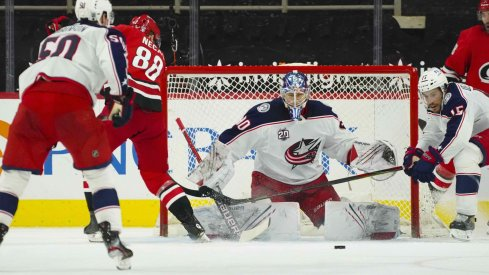 Feb 15, 2021; Raleigh, North Carolina, USA; Carolina Hurricanes center Martin Necas (88) and Columbus Blue Jackets goaltender Elvis Merzlikins (90) watch the puck during the third period at PNC Arena.
