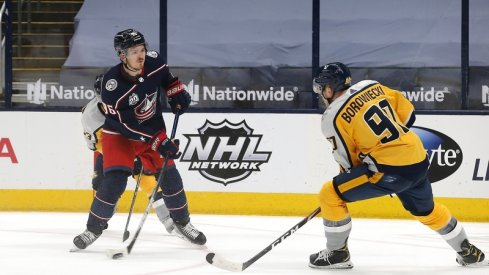Columbus Blue Jackets center Jack Roslovic (96) wrists a shot on goal as Nashville Predators defenseman Mark Borowiecki (90) defends during the third period at Nationwide Arena.