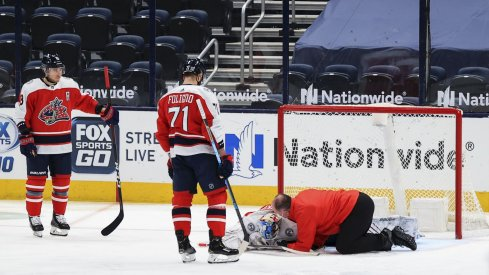Feb 20, 2021; Columbus, Ohio, USA; Columbus Blue Jackets goaltender Elvis Merzlikins (90) is looked after by Columbus head athletic trainer Mike Vogt (right) during a stop in play against the Nashville Predators in the third period at Nationwide Arena.