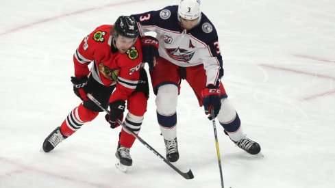 Chicago Blackhawks left wing Brandon Hagel (38) and Columbus Blue Jackets defenseman Seth Jones (3) fight for the puck during the second period at the United Center.