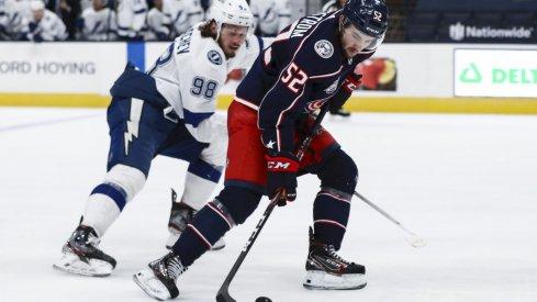 Jan 21, 2021; Columbus, Ohio, USA; Tampa Bay Lightning defenseman Mikhail Sergachev (98) skates as Columbus Blue Jackets center Emil Bemstrom (52) controls the puck at Nationwide Arena.