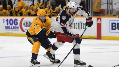 Feb 27, 2021; Nashville, Tennessee, USA; Columbus Blue Jackets right wing Oliver Bjorkstrand (28) takes a shot on goal against Nashville Predators right wing Rocco Grimaldi (23) during the second period at Bridgestone Arena.