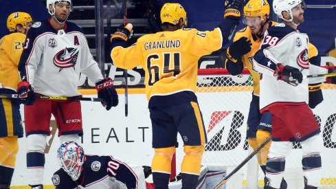 Nashville Predators center Mikael Granlund (64) and center Ryan Johansen (92) celebrate after a goal by right wing Eeli Tolvanen (28) past Columbus Blue Jackets goaltender Joonas Korpisalo (70) during the second period at Bridgestone Arena.