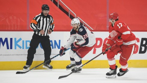 Columbus Blue Jackets right wing Oliver Bjorkstrand controls the puck as Detroit Red Wings defenseman Filip Hronek defends during the first meeting of the season between the two teams.