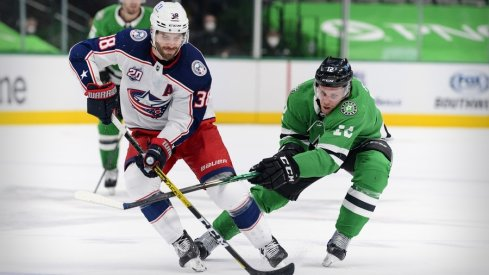 Columbus Blue Jackets center Boone Jenner (38) and Dallas Stars center Radek Faksa (12) chase the puck during the first period at the American Airlines Center.