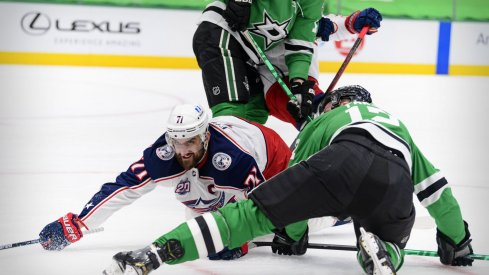 Mar 4, 2021; Dallas, Texas, USA; Columbus Blue Jackets left wing Nick Foligno (71) and Dallas Stars center Radek Faksa (12) fight for the loose puck during the first period at the American Airlines Center.